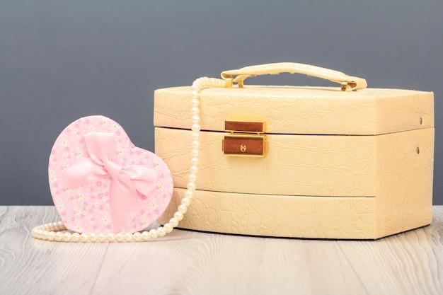 Trousse à cosmétiques et coffret cadeau en coeur pointu sur planches de bois et fond gris. concept de jour de célébration.