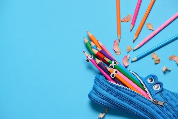 Trousse à crayons drôle mangeant des crayons sur bleu