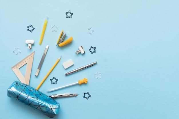 Trousse avec des fournitures scolaires sur une table en bois bleue