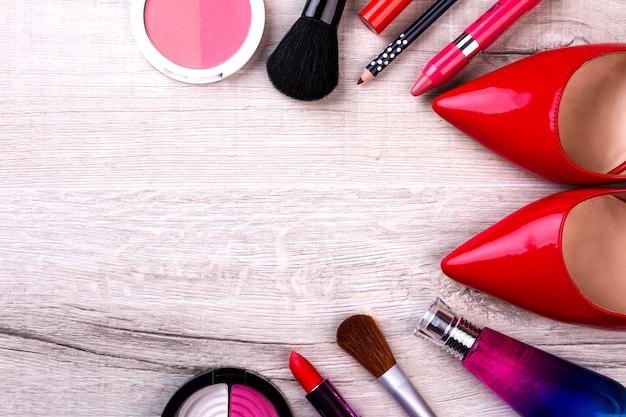 Trousse de maquillage et chaussures rouges. cosmétiques sur fond en bois. début de journée coloré. la beauté sauvera le monde.