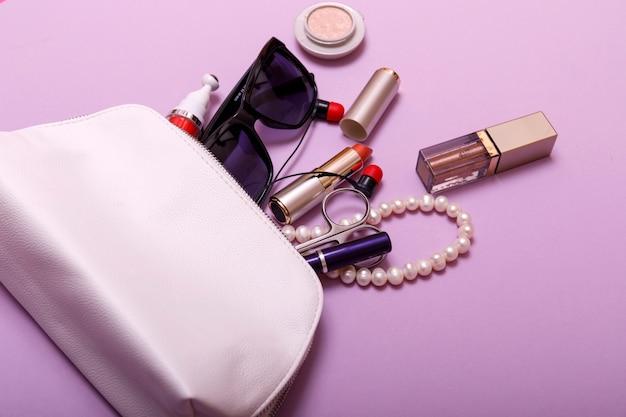Trousse de maquillage avec des produits cosmétiques isolé sur fond rose