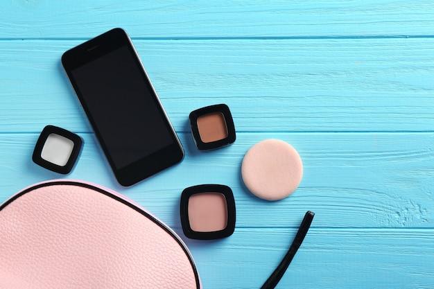 Trousse de maquillage rose avec des cosmétiques décoratifs et smartphone sur table en bois turquoise