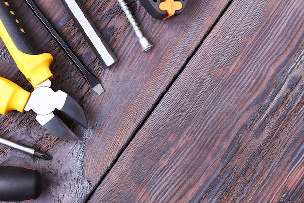 Trousse à outils sur fond de bois. pinces, clé allen et tournevis. outils obligatoires dans le ménage.