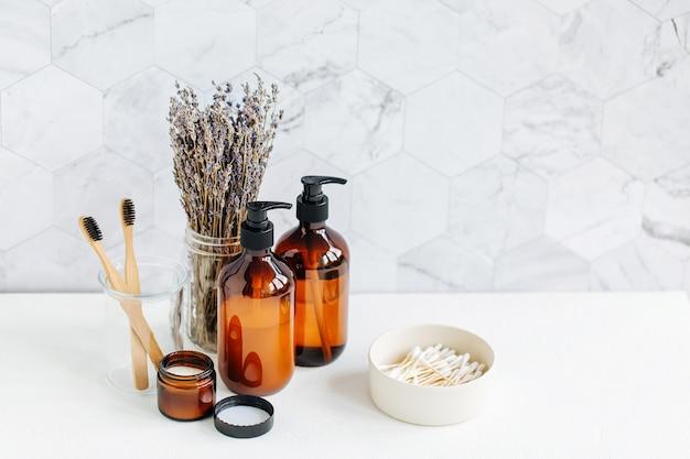Trousse de toilette à la lavande. bouteilles de savon et de shampoing sur table blanche en arrière-plan de la salle de bain.
