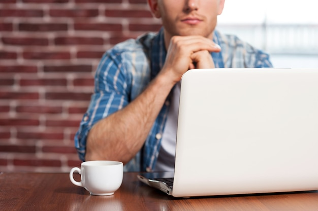 Trouver une solution. gros plan sur un jeune homme assis à la table avec un ordinateur portable dessus