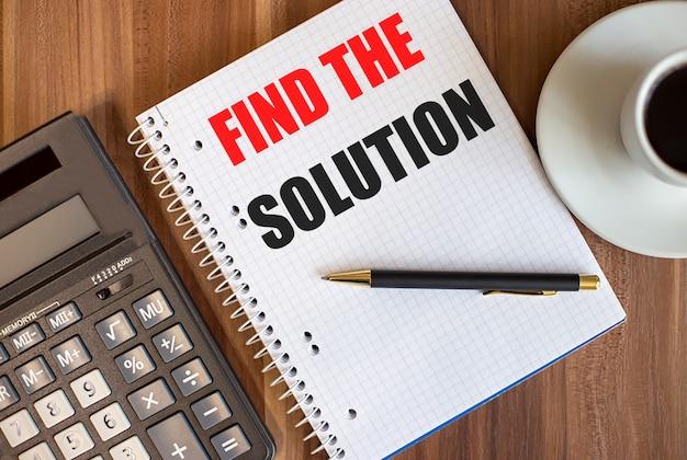 Trouvez la solution écrite dans un bloc-notes blanc près d'une calculatrice et d'une tasse de café sur un fond en bois foncé