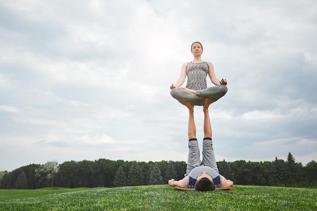 Trouvez votre équilibre trouvez-vous beau jeune couple faisant du yoga acro dans la nature homme fort