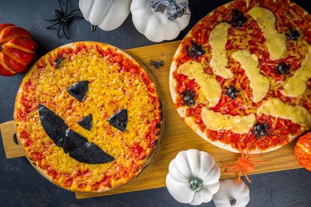 Truc ou friandise de fête d'halloween, pizza effrayante amusante dans le style des personnages d'halloween - chauves-souris, araignées, citrouille jack o lantern, cheddar, mozzarella et fromage noir