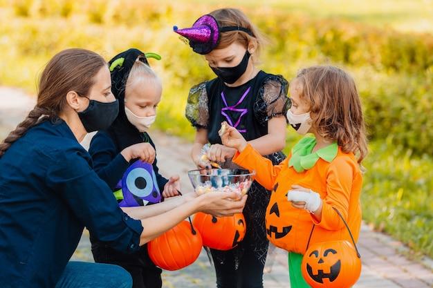 Truc ou friandise pour enfants en costume d'halloween et masque facial protégeant de covid19 happy halloween