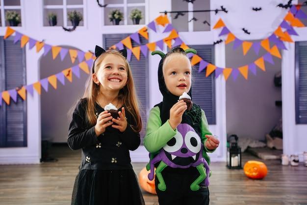 Truc ou friandise pour enfants dans un costume d'halloween et des masques faciaux mangent des friandises et s'amusent à rire