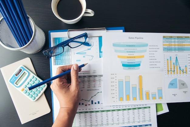 Trucs d'affaires, graphique, graphiques, calculatrice, verres, stylo et une tasse de café.