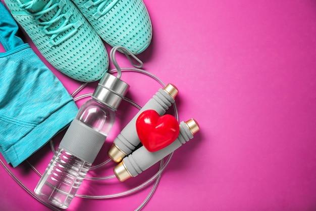 Trucs de gym et coeur rouge sur la couleur.