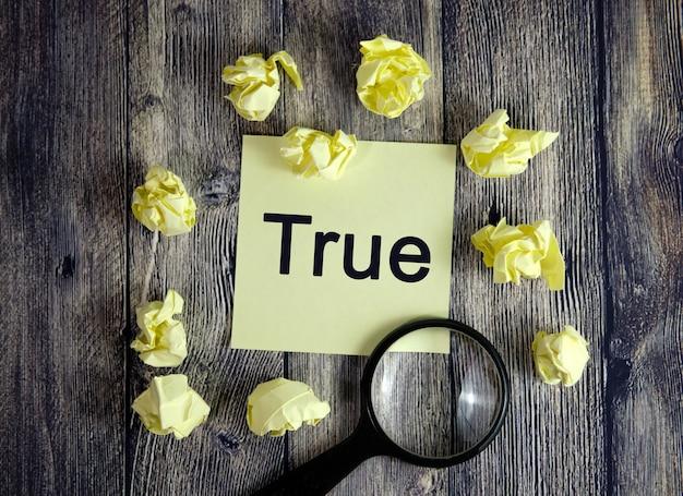 True est écrit sur un autocollant jaune. sélection des faits, recherche avec une loupe