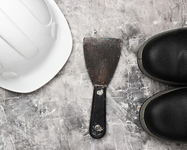 Truelle, bottes en cuir, casque de construction sur fond de béton gris. équipement de constructeur. vue de dessus