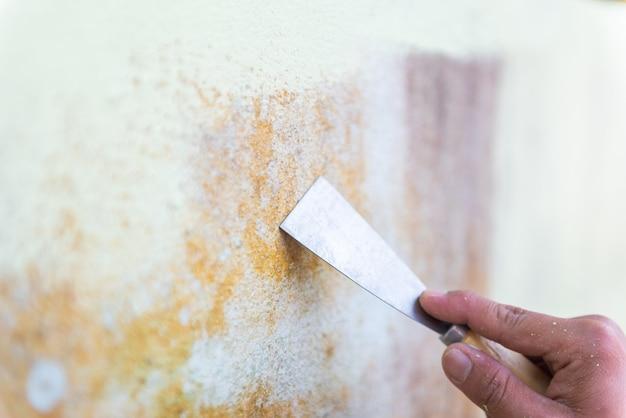 Truelle nettoyant la surface d'un mur