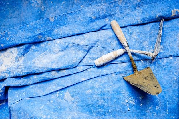 Truelles de ciment sales utilisées par les maçons.