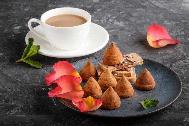 Truffe au chocolat avec morceau de chocolat au lait et une tasse de café sur une assiette en céramique bleue.