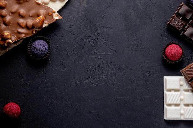 Truffe de bonbons au chocolat avec des morceaux de chocolat et de la poudre de cacao volant sur un fond noir.