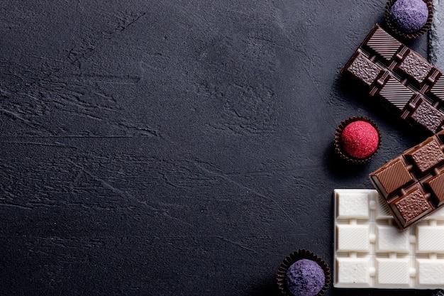 Truffe de bonbons au chocolat avec morceaux de chocolat et poudre de cacao volante sur fond sombre.