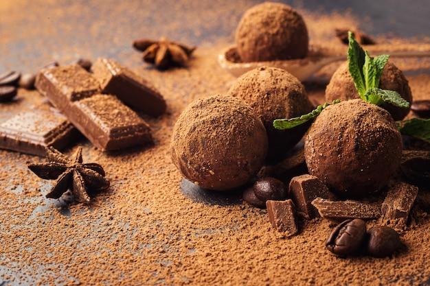 Truffes au chocolat, bonbons au chocolat à la truffe avec de la poudre de cacao.balles énergétiques fraîches faites maison avec du chocolat.truffes assorties gourmandes faites par le chocolatier.des morceaux de chocolat et de grains de café