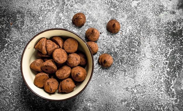 Truffes au chocolat dans un bol. sur une table rustique.