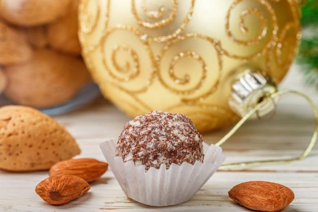 Truffes au chocolat faites maison aux amandes sur une table en bois blanche avec des branches de sapin et des balles de jouets festifs