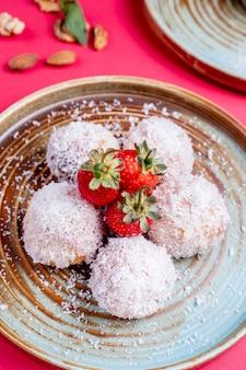 Truffes aux fraises enrobées de copeaux de noix de coco