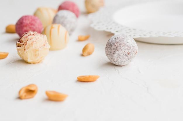 Truffes glacées colorées dispersées sur un tableau blanc