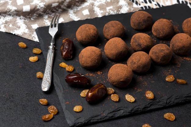 Truffes végétaliennes faites maison avec des fruits secs, des noix et de la poudre de cacao crue servies sur une plaque en ardoise noire