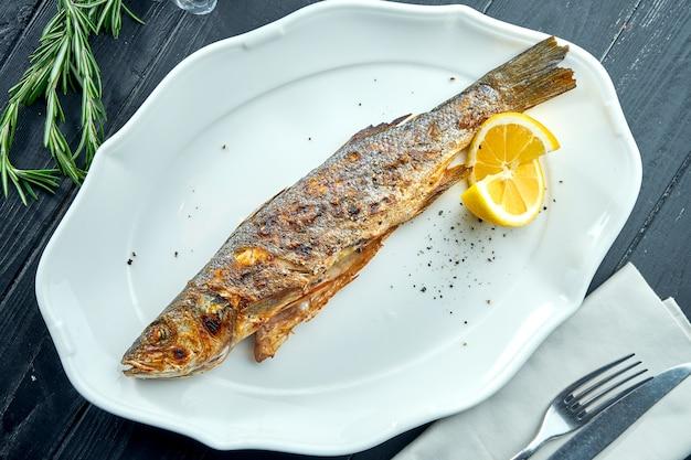 Truite entière grillée au feu de charbon de bois, servie dans une assiette blanche avec du citron sur une surface en bois sombre.