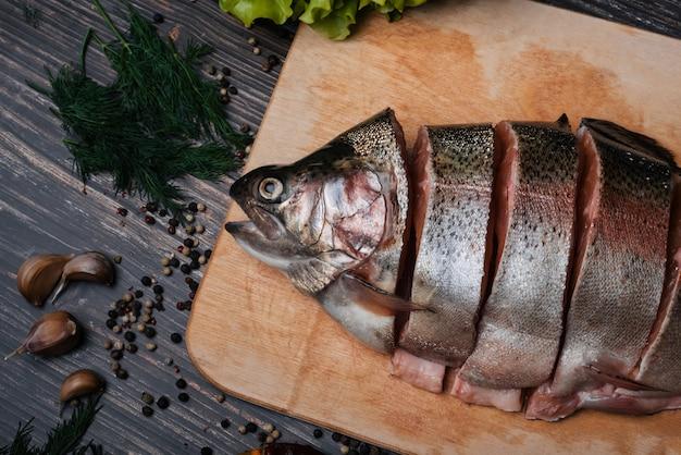 Truite fraîche coupée en morceaux sur une planche de bois pour la cuisson. poisson rouge cru