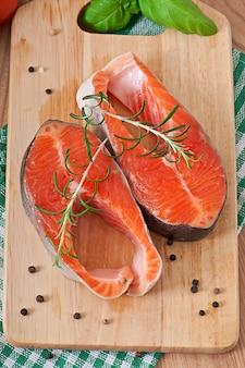 Truite fraîche et crue sur une planche à découper en bois avec tranches de citron, romarin et poivre