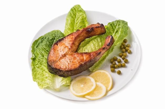 Truite frite avec un morceau de laitue, citron et pois verts sur fond blanc