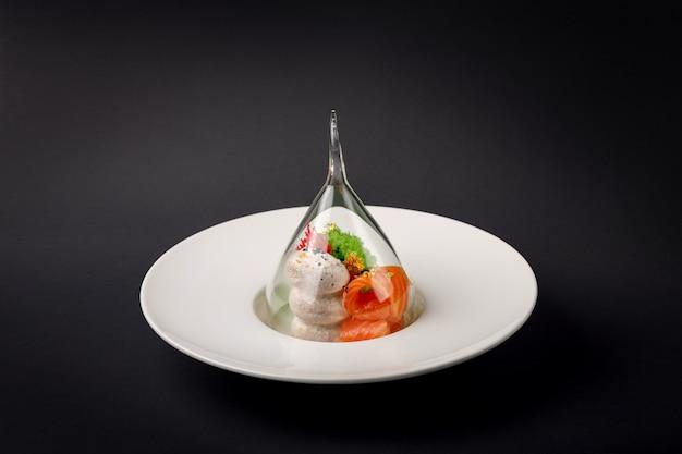 Truite gravlax de cuisine moléculaire avec glace à l'ail sur fond noir