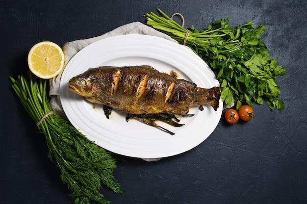 Truite grillée sur une assiette blanche, brins d'aneth et de persil.