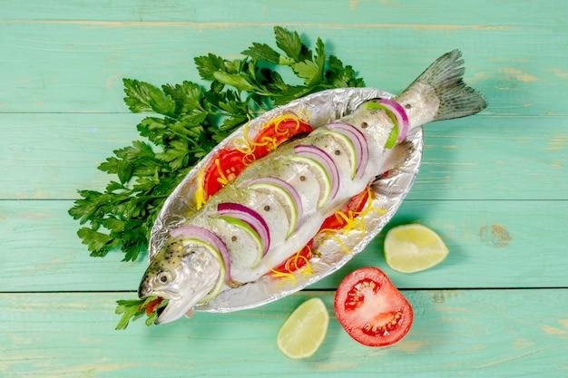 Truite de poisson cru cuit pour la cuisson avec du citron et des tomates sur une plaque avec du papier d'aluminium.