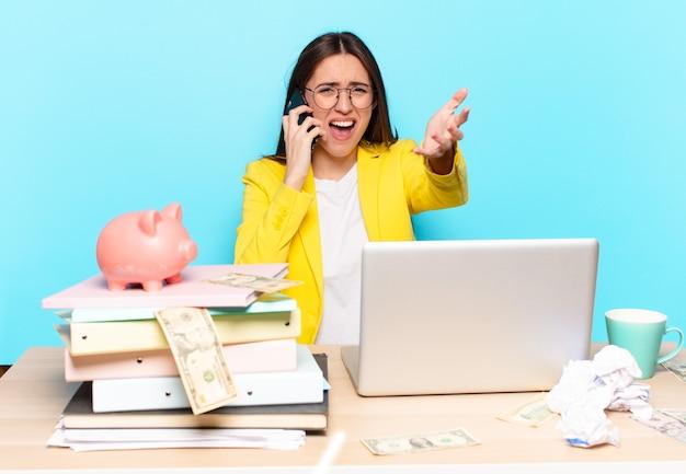 Tty businesswoman assis sur son bureau travaillant avec un ordinateur portable