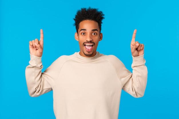 Tu dois essayer ça. sortant étonné et excité heureux souriant homme afro-américain aime les vacances d'hiver, assister à une fête géniale, pointer du doigt vers le haut, s'amuser et parler de promo, mur bleu