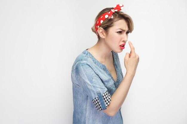 Tu es un menteur. portrait d'une belle jeune femme en colère en chemise en jean bleu décontractée avec maquillage et bandeau rouge debout avec un geste de mensonge et montrant. tourné en studio intérieur, isolé sur fond blanc.