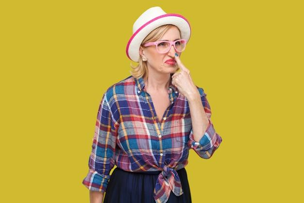 Tu es un menteur. portrait d'une femme mûre élégante et moderne en colère dans un style décontracté avec un chapeau, des lunettes debout regardant et touchant le nez avec un geste de mensonge. studio intérieur tourné isolé sur fond jaune.