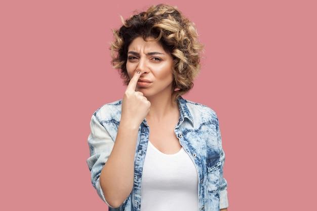 Tu es un menteur. portrait d'une jeune femme sérieuse avec une coiffure frisée en chemise bleue décontractée, debout avec le doigt sur le nez et montrant un geste de mensonge. tourné en studio intérieur, isolé sur fond rose.
