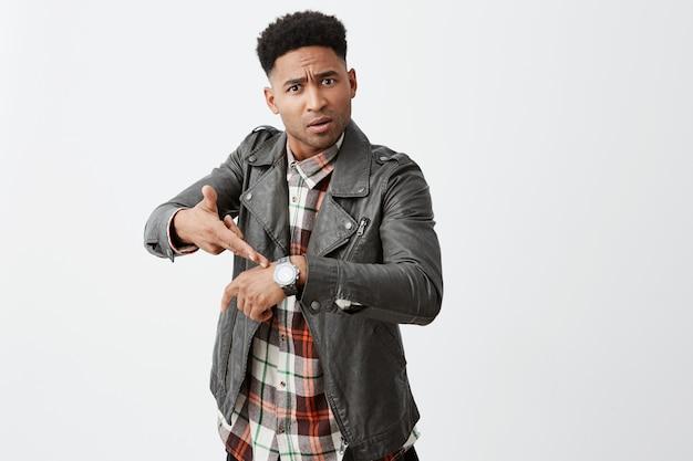 Tu es en retard. portrait d'un beau mec mature à la peau noire en colère avec une coiffure afro en veste de cuir pointant sur la montre avec une expression insatisfaite après qu'un ami soit en retard d'une heure.