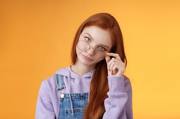 Tu te fous de moi. une sœur aînée agacée et irritée, intelligente et irritée, regarde sous le front des lunettes, des paupières roulent, un sourire narquois, des blagues stupides et énervées, debout sur fond orange.
