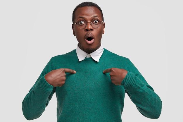 Tu veux dire moi? un étudiant noir étonné se pointe du doigt, regarde avec les yeux grands ouverts, a retenu son souffle, porte un pull