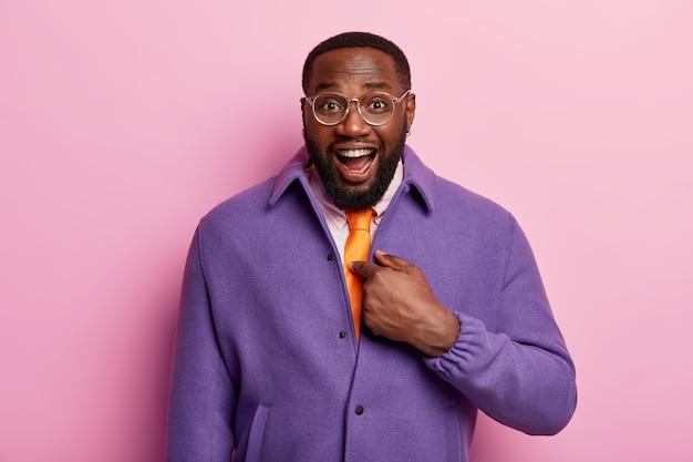 Tu veux dire moi? un homme barbu à la peau sombre et joyeux se montre du doigt, rit joyeusement, se fait prendre, porte des lunettes et une veste violette