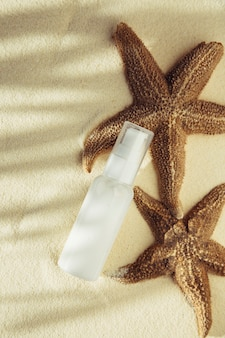 Tube blanc avec de la crème sur fond de sable