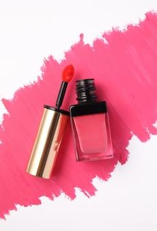 Tube de brillant à lèvres sur fond de rouge à lèvres rose
