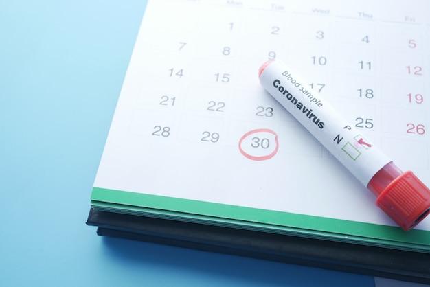 Tube et calendrier de texte de sang de corona sur la table