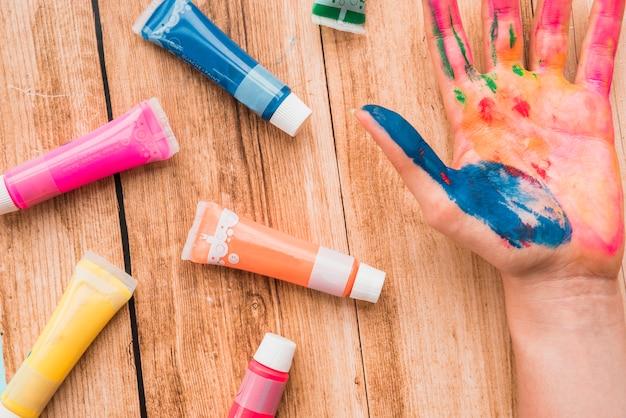 Tube coloré, couleur de l'eau et main peinte sur une surface en bois