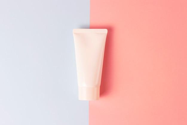 Tube avec de la crème sur un fond bleu et rose, vue de face, concept de soins cosmétiques
